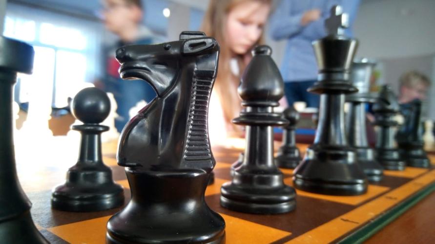 Widok figur szachowych w tle uczestników.