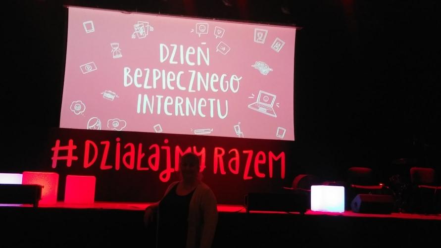 Zdjęcie wystroju sceny z napisem na ekranie projektora DZIEŃ BEZPIECZNEGO INTERNETU i świecący napis #Działajmy Razem.