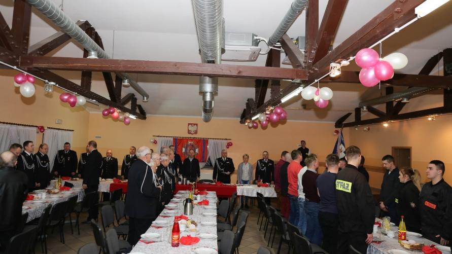 Widok sali z zastawionymi stołami i zasiadającymi strażakami.