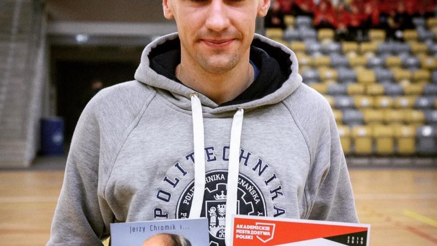 Zdjęcie na sali  Dawida Przybyszewskiego trzymającego dyplom i książkę.
