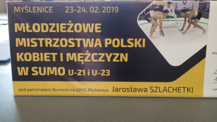 """Plakat z napisem """"MYŚLENICE 23-24.02.2019 MŁODZIEŻOWE MISTRZOSTWA POLSKI KOBIET I MĘŻCZYZN W SUMO U-21 i U-23 pod patronem burmistrza UMiG Myślenice Jarosława SZLACHETKI"""""""