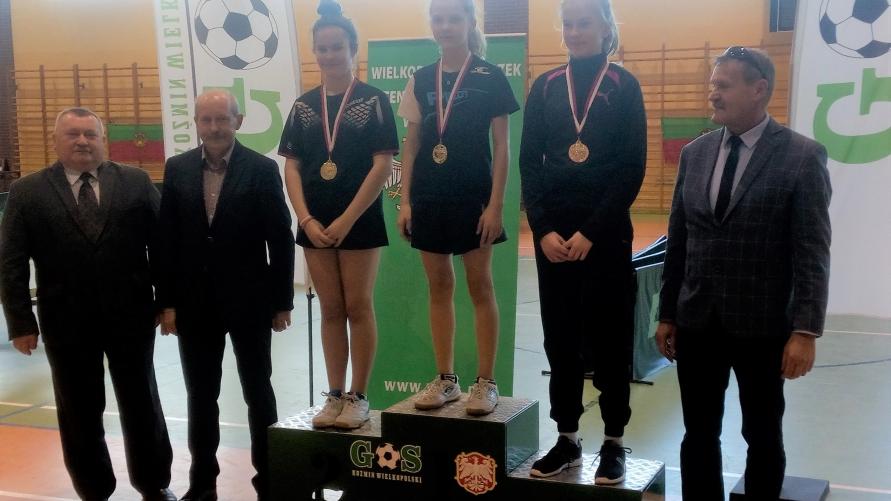 Zdjęcie grupowe zawodników na podium w sali sportowej.