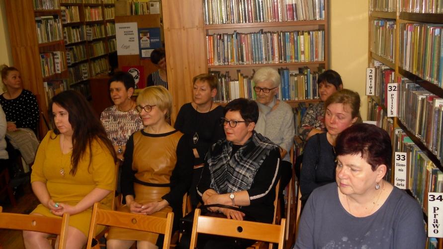 Widok siedzących gości w bibliotece.