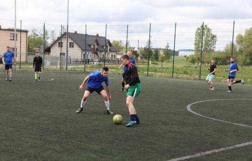 Zawodnicy grający w piłkę na murawie.