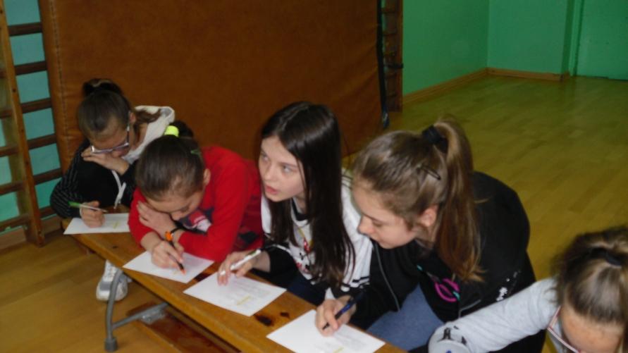 Dzieci piszące na kartkach na ławeczce.