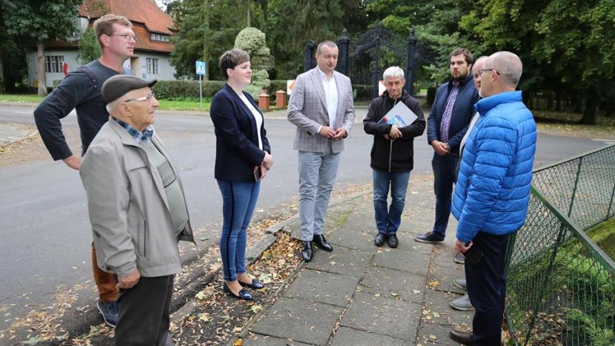 dorosłe osoby stoją przy chodniku