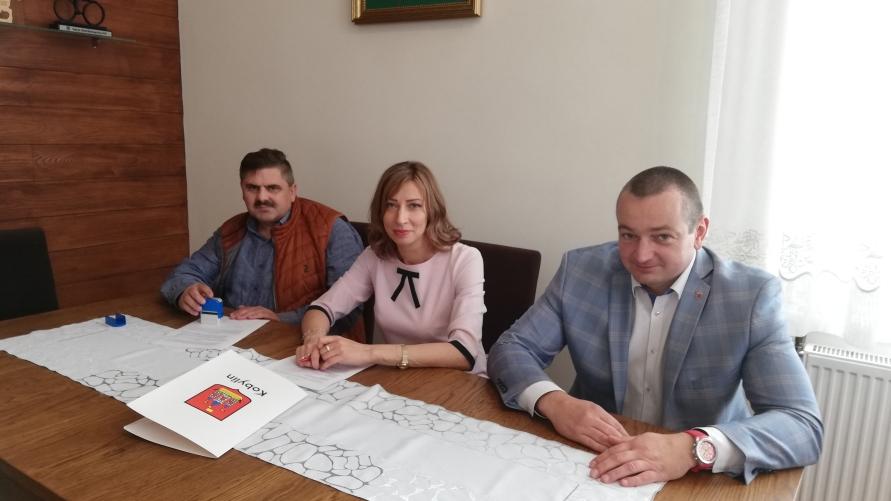 Trzy osoby siedzą przy stole i podpisują umowę