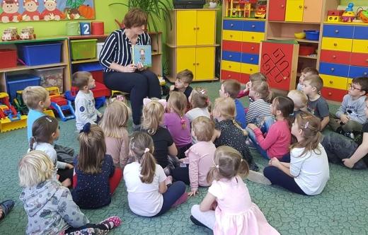 Dzieci siedzące na podłodze w bibliotece.