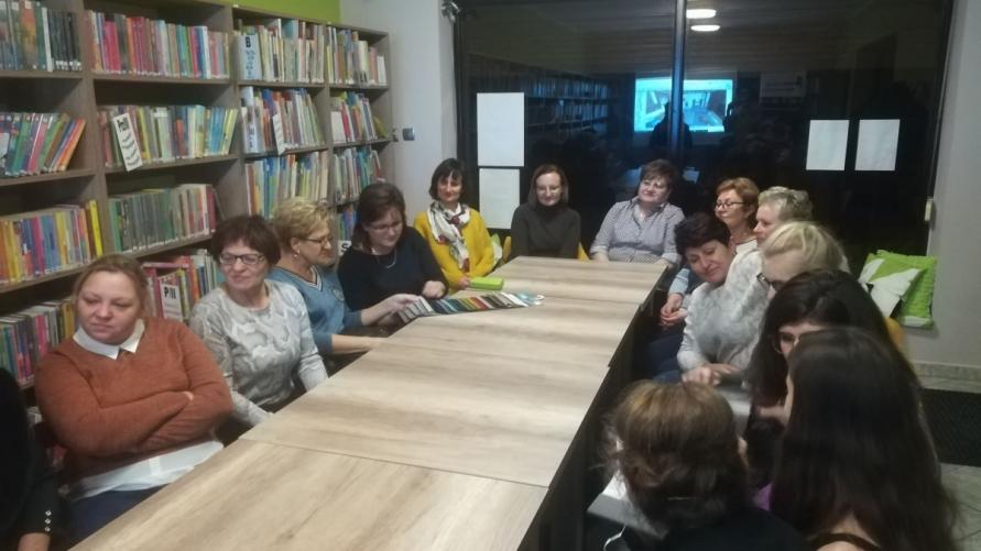 Widok siedzących osób w bibliotece.