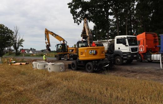 Grafika przedstawia sprzęt budowlany oraz rury do kanalizacji