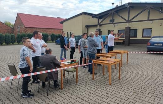 grafika przedstawia uczestników strzelania na tle sali wiejskiej w Zalesiu Małym.