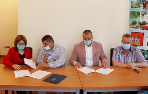 cztery osoby podpisują umowy