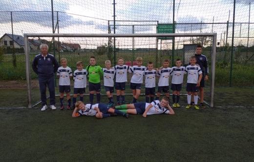 Grafika przedstawia 10 dzieci oraz 2 osoby dorosłe na boisku. Grafika została wykonana na tle bramki piłkarskiej.